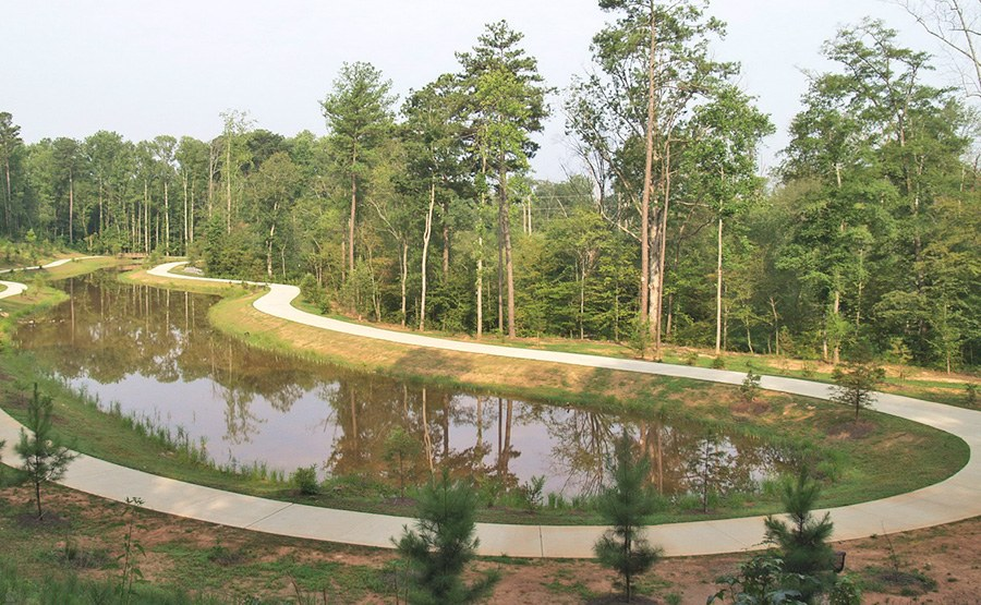 The naturalized wet pond is commingled with a walking trail. The pond provides storage and treatment of runoff, and a reservoir for groundwater infiltration and base-flow augmentation in Big Creek.