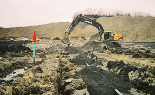 Installation of a geotechnical monitoring program at the base of a monitored preload fill. Photo shows installation of an 800-foot-long profiler pipe adjacent to a line of settlement plates.
